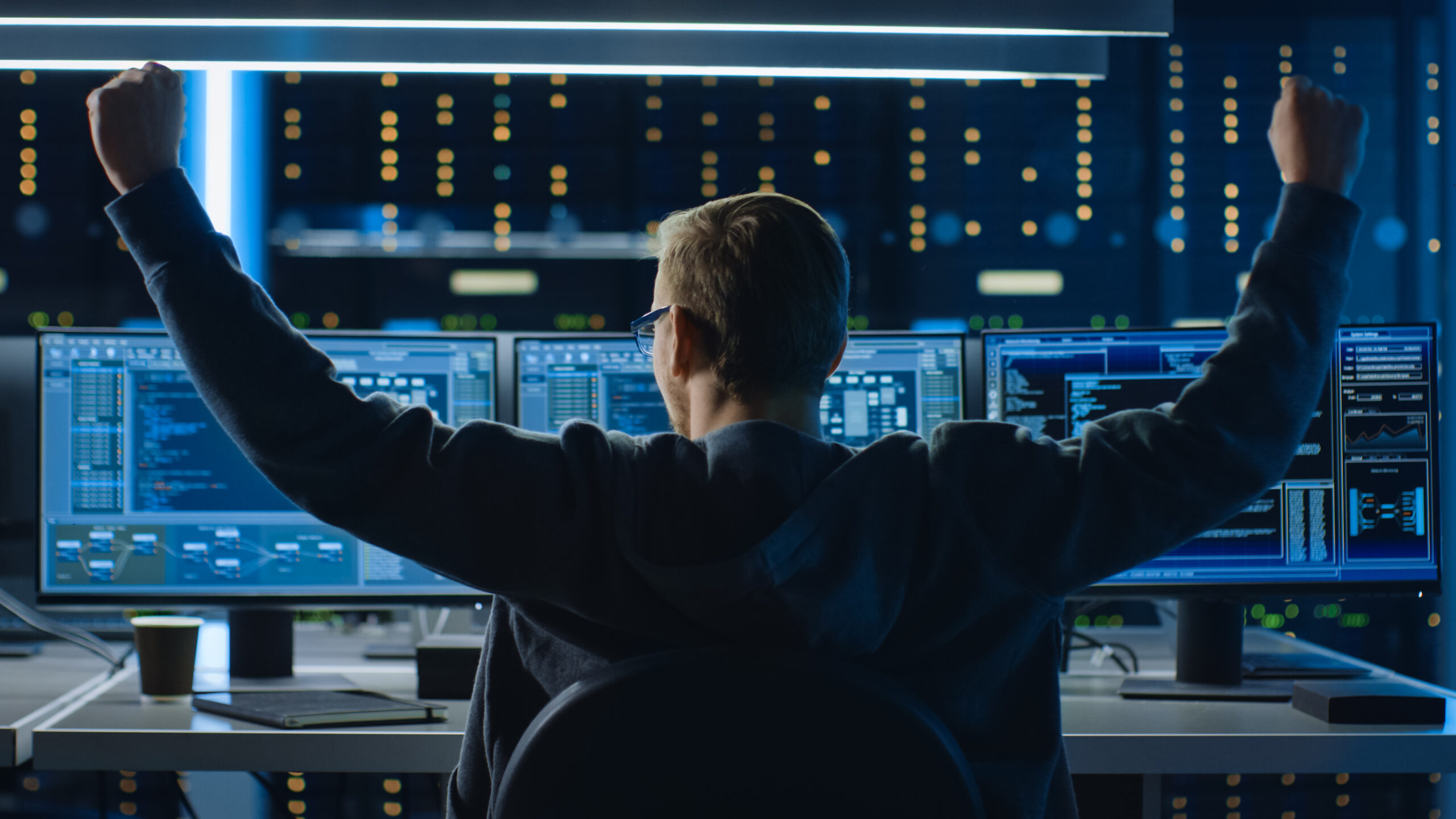 IT Specialist Working on Personal Computer with Monitors Showing Coding Language Program, He Celebrates His Success by Doing YES Gesture. Technical Room of Data Center.